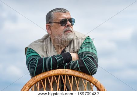 Outdoor portrait of senior man in black sunglasses leant on a wicker chair back and looking