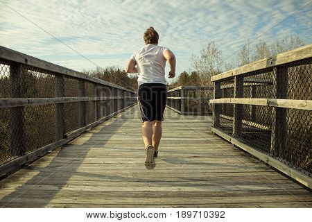 Male Running To Lose Weight. Slightly overweight male running on a boardwalk in an attempt to exercise and lose weight.