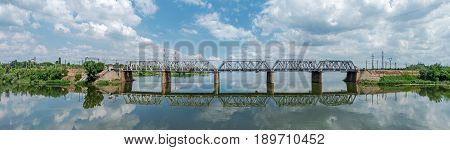 Panoramic view of the railway bridge across the river in late spring