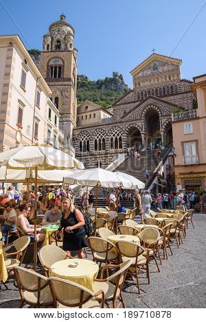 Amalfi Italy - September 1 2016: Tourists visit cafe on the Piazza del Duomo in front of Amalfi Cathedral.