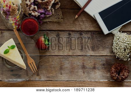 Cafe background with copy space. Crepe cake strawberry sauce on rustic wood background. Relaxing with delicious cake and use smart phone for work or entertain. Lively background with copy space. Vintage background concept.