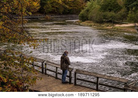 Michigan Salmon Fishermen. Male salmon fishing in the autumn on the shore of a Great Lakes tributary river in Ludington Michigan.