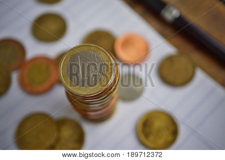 Macro detail of a silver and golden coin in a value of one Euro (European currency, EUR) on the top of coins' pile in a business background white lined pad, black pen a randomly spread small change