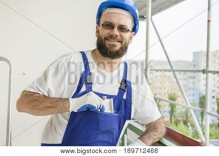 A construction worker in a work outfit, protective gloves and a helmet on his head pulls a silver hip-flask his pocket, looking back. Work at high altitude. Scaffolding in the background.