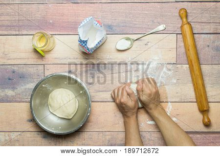 Kneading the dough to cook the cake on wooden table