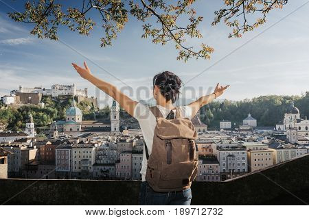 Austria. Salzburg. A young tourist girl with arms raised and admiring looks at the historic city center of Salzburg World Cultural Heritage UNESCO