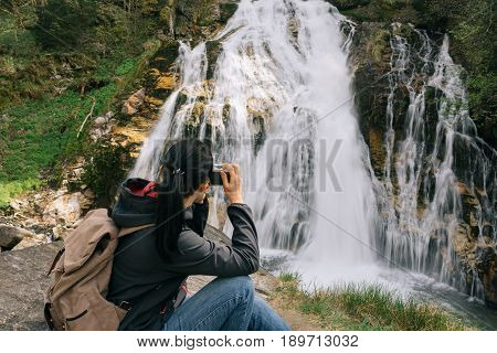 Austria. Bad Gastein. A Girl With A Camera By The Waterfall In The Alpine Mountains