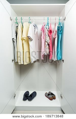 Clothes hanging on rail in white wardrobe. Men's and women's summer clothes and shoes pastel colors