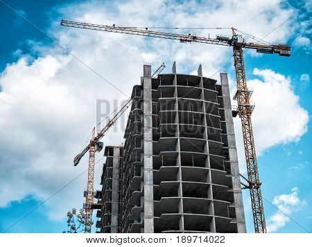 Two Crane near construction building on blue sky background.