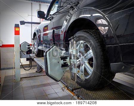 MOSCOW, MAR,02, 2017: Car automobile wheel alignment maintenance works repair at automotive service center workshop. Technical maintenance wheel alignment correction fixation MOT. Car maintenance