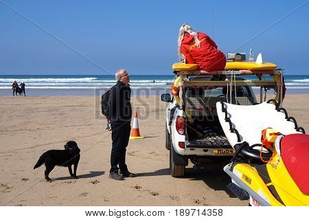 Newquay, Cornwall, Uk - April 7 2017: Female Rnli Lifeguard Talking To A Man With A Dog On A Surfing
