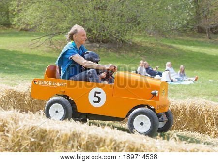 STOCKHOLM SWEDEN - MAY 21 2017: Smiling boy and granpa driving a orange soapbox car downhill on a field in the race Gardesloppet at Djurgarden Stockholm Sweden. May 21 2017
