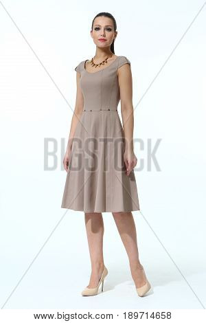 fashion model in summer biege short midi dress and high heel shoes full body photo isolated on white