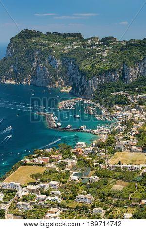 aerial view of italian holiday island Capri with picturesque marina and Tyrrhenian sea in background, Capri island, Campania region, Italy