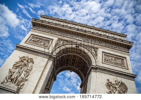 The Arc de Triomphe in Paris against a blue sky