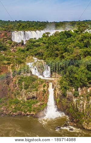 The concept of extreme and exotic tourism. Several picturesque waterfalls. Iguazu Falls National Park - grandiose complex of waterfalls on the border of Argentina, Brazil and Paraguay