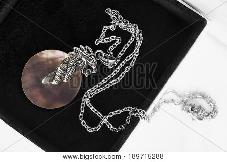 Silver dragon medallion on a chain in black jewel box closeup