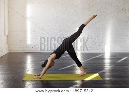 Beautiful young woman in sportswear practicing yoga asana Eka pada Adho Mukha shvanasana. Pretty asian girl practices Three-Legged Down Dog Dissected in modern yoga hall early morning. Yoga concept