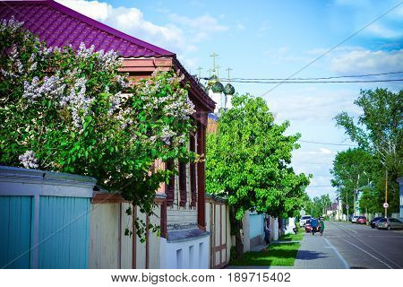 Kolomna, Moscow region - June 03, 2017 - The street of old Kolomna with house, lilac, walking people, road, cars and church. Summer blossom for posters, prints, calendars, interior decoration, design.