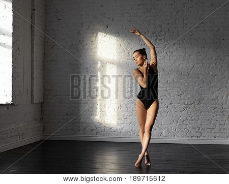 Asian dancer female engaged in modern ballet in the beautiful dancing hall. Young slim woman dancer posing against white brick wall in rehearsal room. Body ballet concept