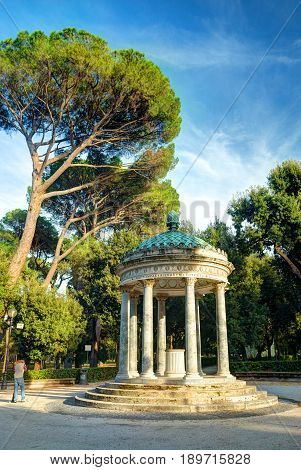 ROME, SEP 15, 2006: Antique summerhouse pavilion garden-house among tropical trees in Villa Borghese city garden park. Summerhouse antique Italian architecture Rome holidays vacation tours travel trip