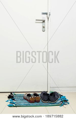 Colorful asian floor mat near white door. Vertical shot of an closed wooden front door without windows. Two pairs of shoes