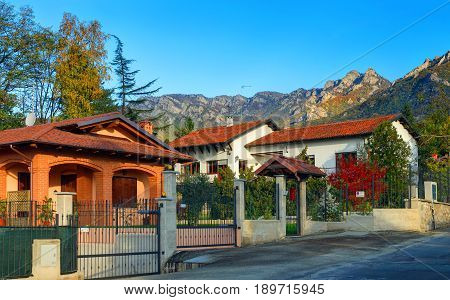 View on classical Italian Swiss cottage chalet style summer houses architecture in Alpine mountains near to Turin. Italian private houses in Alps. Holiday resort. Italy holidays vacation tours