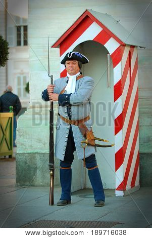 TURIN, ITALY, NOV, 21, 2007: Guardian with musket rifle in guard house. Weekend parade of old Italian guards army in gray uniform on Turin Piazza Castello. Italy holidays vacations