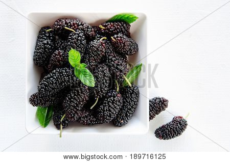 Fresh ripe mulberries with mint in bowl on white background, copy space. Horizontal, top view