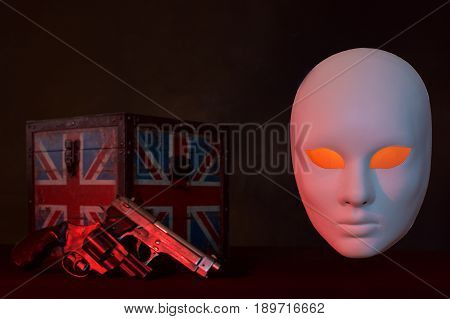 Concept of terrorism.England flag box, guns and mask on dark background