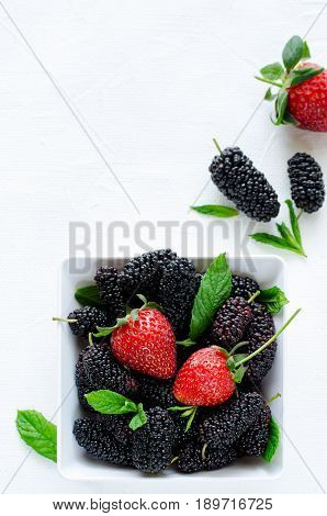 Fresh ripe mulberries and strawberries with mint in bowl on white background, copy space. Vertical