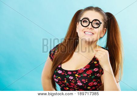Happy Teenage Woman Holding Fake Eyeglasses On Stick
