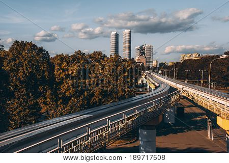 View of empty overground elevated monorail junction in metropolitan city with two twins skyscrapers and