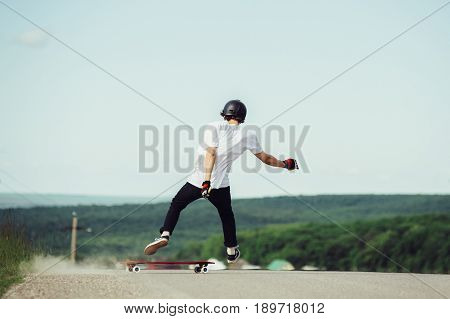 A young hipster in a helmet and gloves performing a slide standing at a high speed falls from the board. Epic crash