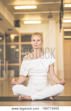 Beautiful Young Woman Sitting In Lotos Pose And Practicing Meditation In Yoga Hall