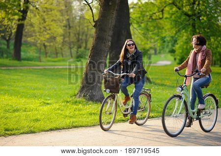 Two young women ride bikes in the spring park. Gentle spring greens yellow dandelions clean air. Pleasure by nature and movements. Healthy lifestyle.