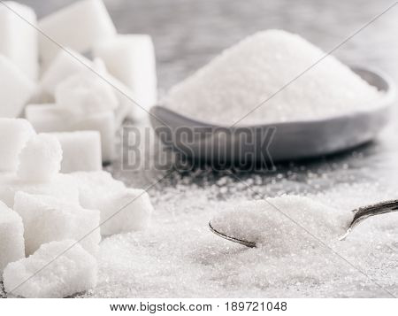 Sugar background. Sugar cubes, granulated sugar in spoon and plate. White sugar on gray galvanized iron background. Copy space.