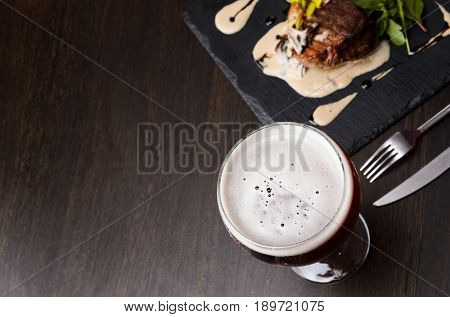 Beer glass and steak on black table, view from above.