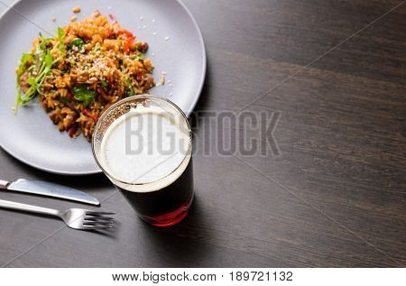 Beer glass and food on black table with food, view from above.