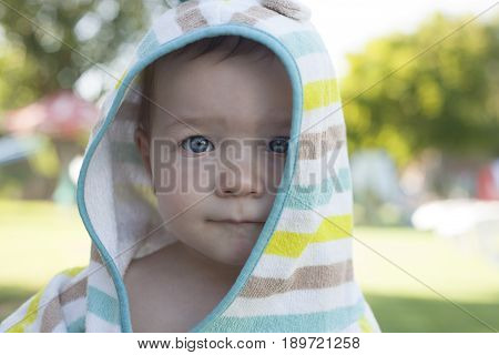 1 year baby boy with hooded poncho towel after swimming. Portrait