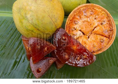 Fresh beal fruits on a banana leaf. Half cut beal fruit. Slices of fruit marmalade from dry beal fruits. Sweet candied beal fruits.