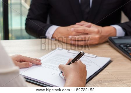 Woman signing contract or loan agreement document with businessman waiting for