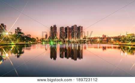 Sunset At A Lake Of A Park With The City On Background