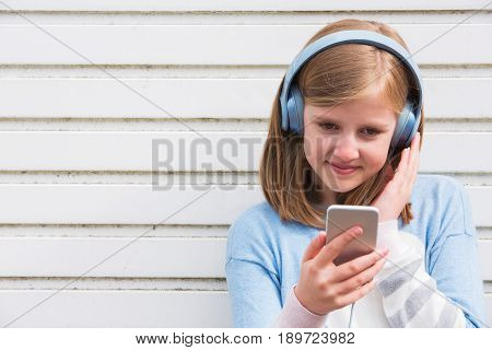 Pre Teen Girl Wearing Headphones And Listening To Music In Urban Setting