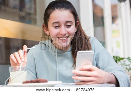Young Girl At Cafe Reading Text Message On Mobile Phone
