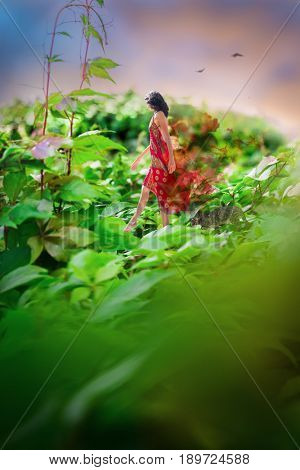 A young sexy woman in a red dress daydreams amongst animals as she gracefully steps on the delicate vine of her fantasy world
