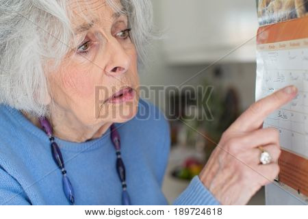 Confused Senior Woman With Dementia Looking At Wall Calendar