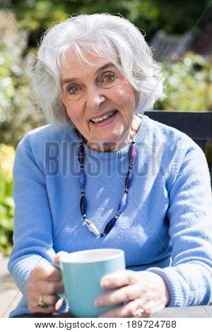 Portrait Of Senior Woman Relaxing In Garden With Hot Drink