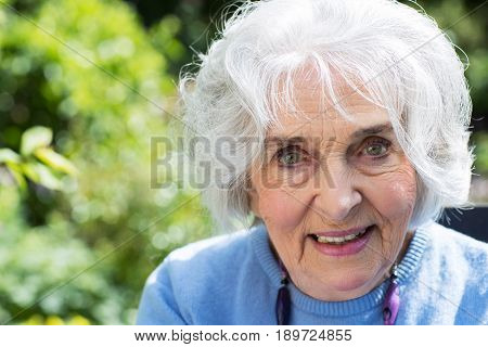 Portrait Of Senior Woman Relaxing In Garden