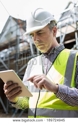 Architect On Building Site Using Digital Tablet